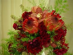 Soft red protea mixed with textural foliage, cymbid orchids, dahlias and celosia designed in a crescent shape.  www.opulencefloral.com
