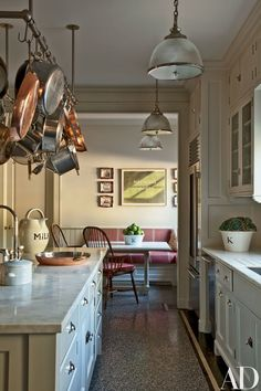The kitchen's pot rack and pendant lights, all by Ann-Morris Antiques, are installed over counters of Calacatta Sponda marble.