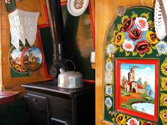 wood stove in a narrow boat galley.  The arched pannel painted with a castle folds down to be a table, and hides a little cabinet.