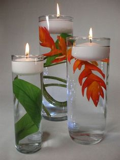 DIY How to Make a Floating Candle Centerpiece...Use three cylinder vases (different sizes) and place the appropriate width floating candle in each. Place a faux helicona blossom and leaves in the vase. Use wire cutters to cut off the long stem. The lighting effect comes for a vase illuminator. Place a tulle circle over the illuminator to match you wedding colors or the table cloth colors.