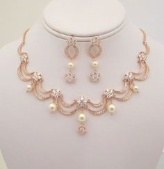 This beautiful Rose gold Bridal necklace and earring set is created with rose gold plated components set with Swarovski Pure Brilliance cubic zirconia stones and finished with Swarovski pearls. This is such a romantic design that sits high on your neck. Necklace measures 17 inches and extends to 20 inches. Earrings dangle 1-1/2 inch from stud to bottom of rhinestone flower. ** Last photo shows the version without pearls. This is an original design by © Treasures by Agnes PLEASE ALLOW ...