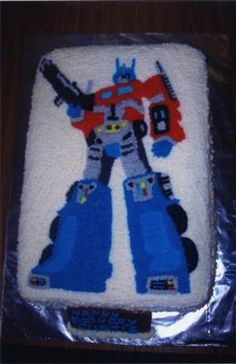 optimus prime transformer:  Made 3 buttercake mixs  in a 14inch cake tin.  I used Buttercream icing on the cake, then traced a picture. Then I pin pricked the design onto the cake