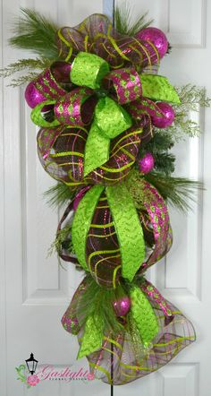 Love color for the Christmas holidays other than the traditional red and golds, look no further. Christmas teardrop swag in vivid fuchsia colors and deco mesh by Gaslight Floral Design. GaslightFloralDesign.com