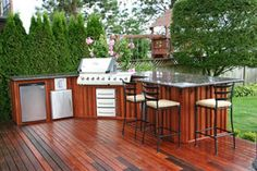 wood and deck, a little dark. i do like the layout of fridge and bbq though. Could have bbq in corner of deck area?