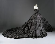 In this design, John Galliano for Dior combined the elements of a <I>robe à la française</I> with the vast crinolined silhouettes of the mid-nineteenth century. The stomacher, open overskirt, and petticoat are expressly eighteenth century, but the huge wired cages that support the skirts over nine feet wide are constructed more like the hoops of the Second Empire than the discrete by comparison panniers of the ancien régime