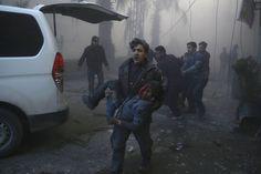Un joven ayuda a un niño herido en un ataque en la ciudad siria de Hamouria, en la zona oriental de Ghouta, un bastión rebelde al este de Damasco.