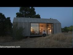 Made of concrete/resin/wood exterior - Portable home - YouTube ( Like how all its window and door have outer panels that open up. I would put the cooktop in the center, and move the fridge to the far left of that wall-- to accommodate a taller rv fridge. If possible, I would have a slated roof, which is more kin to this style of small structure-- more modern to go with the lines of the concrete exterior.)