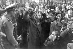 Budapest, Hungary, Jews being humiliated by members of the Arrow Cross Party. SS soldiers and German policemen appearing in the photograph were brought to the site to keep order. The Germans took control of the situation after approximately 24 hours and sent the Jews to their homes. The deportation began only two weeks later, when Eichmann's staff finished all the necessary arrangements. Information source: Janos Varga, director of the Hungarian Film Archives.