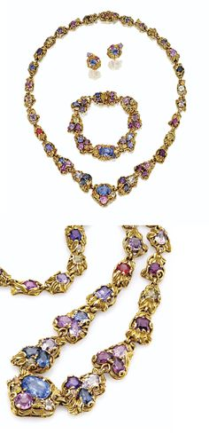 TIFFANY & CO., DESIGNED BY LOUIS COMFORT TIFFANY, CIRCA 1910.  Comprising a necklace, a bracelet and a pair of earrings, formed of sculpted gold links of foliate and scroll design, set with a variety of colored stones, including sapphires in multiple hues, blue and purple spinel, pink tourmaline, amethyst and zircon, in round, cushion and various fancy shapes, lengths of necklace and bracelet 18½ and 6 7/8 inches, earrings with later-added backs, signed Tiffany & Co.
