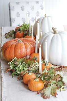 Long white candles amongst various pumpkins and autumn leaves create an elegant glow on your dining table.  Get the tutorial at Ella Claire Inspired.