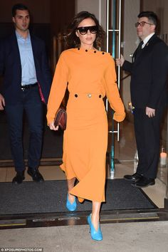 Victoria Beckham was seen leaving her New York hotel in a glamorous orange dress today aft...