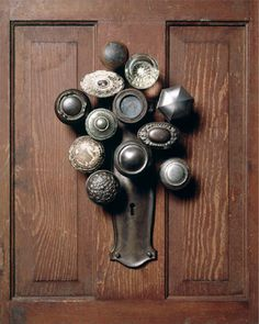 Doorknobs on a wood panel hanging around a keyhole made to look like bouquet