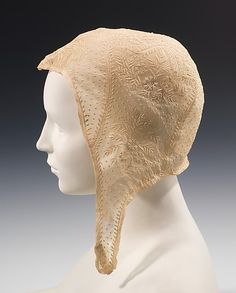 "Cap, 1810–20, American, cotton  ""The close-fitting helmet shape of this cap was one of several fashionable headwear silhouettes of the first decade of the 19th century. The look would have been completed by small curls framing the face. It might also have been worn under a larger bonnet, which produced a different upper silhouette.  The geometric piecing and allover intricate embroidery pattern are typical of the best examples of the empire period's embroidered cotton garments and…"