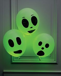 snap one or two green eight-hour light sticks so they glow, and insert them into a white balloon. Inflate the balloon and tie it closed. Use a black marker to draw a wide-eyed visage.