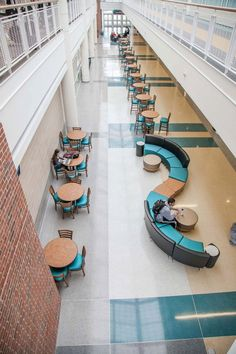 Students lounge in a space inspired by Coastal Carolina University's colors, Teal and Bronze. The school's colors are reflected in the light browns, gray, and teal colors of the terrazzo floor and furnishings. - Carolina Coastal University #terrazzo #getfloored