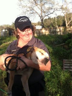 Animal Control officer cradles a dog rescued from a suspected dog fighting ring. He looks quite happy about it.