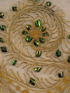 Close-up on a piece with beetle wing embroidery.