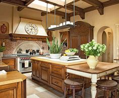 A central skylight sheds light on this otherwise-windowless cooking space where furniture-style details, multiple cabinet finishes, and distressed stone accents establish a warm, Tuscan-style atmosphere: http://www.bhg.com/kitchen/color-schemes/neutrals/beautiful-kitchens-with-natural-colors/?socsrc=bhgpin052814tuscanflair&page=15