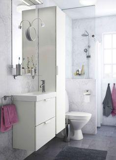 Pieni valkoinen kylpyhuone, jossa valkoinen korkea kaappi, peili ja kahden laatikon allaskalustekokonaisuus.