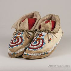 "Cheyenne woman's pair of moccasins with the ""keyhole"" design. The beadwork is done in white, blue and orange solid colored beads and clear red beads."