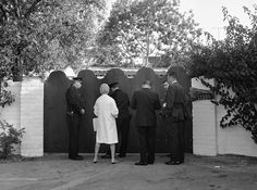 Associated Press.  FILE - In this Aug. 5, 1962 file photo, police officers and newsmen stand at the driveway gate to the home of Marilyn Monroe after she was found dead in her bedroom. The Spanish-style one-story house is in the Brentwood area of Los Angeles. The first police officer on the scene later said he saw her housekeeper using the washing machine in the hours after the actress' death. (AP Photo/Harold Filan, File)