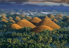 """Chocolate Hills, Bohol, Philippines - These conical limestone mounds are covered in grass that turns brown in the dry season, giving the hills their """"chocolate"""" moniker. Over such formations exist in Bohol province, standing 100 to 300 feet tall. Voyage Philippines, Bohol Philippines, Philippines Travel, The Tourist, Tourist Spots, Places Around The World, Around The Worlds, Chocolate Hills, Chocolate Mountains"""