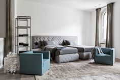 MERIDIANI I TUYO bed with maxi quilted headboard and twin single bases I HARDY bookcases I BELMONDO small armchairs I LALIT rug