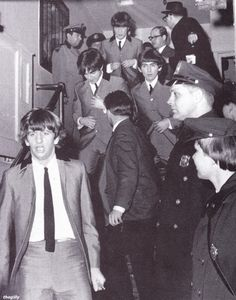 A police guard escorts the Beatles from New York's Carnegie Hall. 12 February 1964