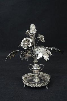 Paliteiro de prata brasileira representando ânfora com flores. Base em salva. Alt. 22 cm.