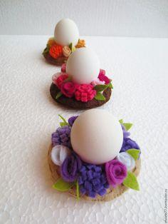 В последние годы появилось множество идей украшения и декора пасхальных яиц. Хочу поделиться с вами еще одним вариантом декора подставок для пасхальных яиц. Итак, приступим. Материалы и инструменты: фетр жесткий толщиной 1 мм и фетр мягкий толщиной 1 мм; ножницы маленькие; нитки; клеевой пистолет или клей; наполнитель (синтепон или холлофайбер); маленькая английская булавка.