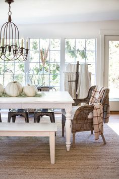 Farmhouse/Cottage style fall home tour... white painted furniture, wicker chairs and pumpkins decorate the dining room here...