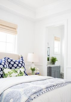 Lovely bedroom features upper walls painted white and lower walls lined with beadboard trim lined with a Restoration Hardware Warner Fabric Bed With Footboard With Nailheads dressed in a white and navy duvet and shams as well as a John Robshaw Lapis Quilt and a Peter Dunham Fig Leaf pillow next to a round mirror and brass bedside table, Worlds Away Lenora Side Table, and a white milk double gourd lamp.