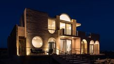 The geometric architectural shapes of the house are particularly pronounced at night Concrete Cover, Rammed Earth Wall, Arch Doorway, Best Architects, Storey Homes, Thatched Roof, Mexico Vacation, Ground Floor Plan, Baja California