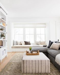 Restful Neutral Living Room Decor With A Built In Window Seat And Bookcases