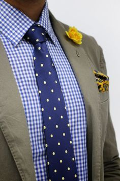 Tap into refined, elegant style with an army green cotton blazer and a white and blue gingham dress shirt.   Shop this look on Lookastic: https://lookastic.com/men/looks/blazer-dress-shirt-tie/14431   — Yellow Floral Lapel Pin  — Navy Polka Dot Tie  — Green-Yellow Paisley Pocket Square  — Olive Cotton Blazer  — White and Blue Gingham Dress Shirt
