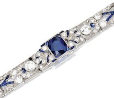 [DETAIL] PLATINUM, SAPPHIRE AND DIAMOND BRACELET, CIRCA 1920    The ornate openwork links set with a cushion-shaped sapphire weighing approximately 2.50 carats, and an old European-cut diamond weighing approximately .95 carat, set throughout with old European-cut and single-cut diamonds weighing approximately 5.50 carats, accented by calibré-cut sapphires, length 7¼ inches, maker's mark, numbered 1604, one small diamond and one sapphire missing.