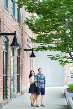Uptown Columbus Georgia Brick Building Southern Charm Plaid Shirt Skirt and White Top Smiling Engagement Photo | www.hannahandrandall.com