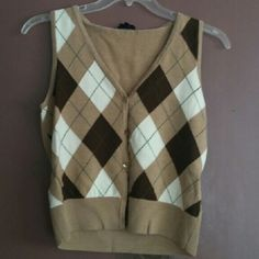 Talbots Merino Wool Diamond Print Sweater Vest Talbots tan, creme & brown diamond print argyle sweater vest cardigan, beautiful neutral colors. Soft and luxurious and made of 100% Italian merino wool, size medium and in great shape, does have 2 tiny pin dot size holes in the back, not really noticable and are very small, gorgeous staple piece! Retail $98, priced accordingly and sold as is Talbots Sweaters Cardigans