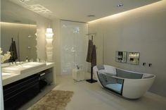 Sala de Banho, da decoradora Dênia Diniz. Adoro banheiros assim, amplos e claros! O piso e as paredes foram revestidos com porcelanato na cor gelo. Atrás da bancada, que é de Magic Stone, a parede foi revestida com um revestimento cerâmico madrepérola.