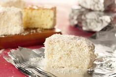 Umedeça os pedaços de bolo na calda e em seguida passe pelo coco ralado. Embrulhe com papel alumí...