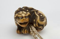 Netsuke of recumbent lion 伏獅子象牙彫根付 銘 「白龍」 Place of Origin: Japan Artist: Hakuryu (Japanese) Date: approx. 1800-1868 Historical Period: Edo period (1615-1868) Object Name: Netsuke Materials: Ivory with dark detail staining and inlaid mother-of-pearl