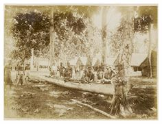 Samoan men and boys stand in and beside a newly dug out wooden canoe. The canoe is balancing on tree trunks and is within a forested area. A row of huts stand behind them. A boy in leaning against a tree in the foreground. Samoa Unknown, 1889, Photograph