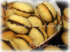 Baci di Dama Baci di dama: deliziosi dolcetti alle mandorle accoppiati a due a due con cioccolata fondente. Per questi biscottini si può variare la preparaz