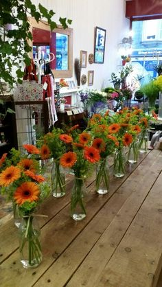 Table arrangements in milk bottles with orange gerbera and mixed foliage.