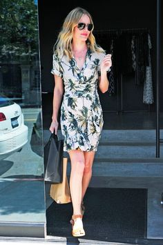 Kate Bosworth wears a printed dress, brown leather sandals, and aviator sunglasses