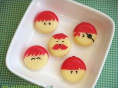 """Babybel Cheese Boys. The black stuff is not a food marker but some seaweed. There's also a picture using """"brown mustard seeds"""" for eyes. If this works with food markers, refer to her site for Babybel Cheese Girls."""