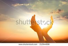 hands holding the sun at dawn - stock photo