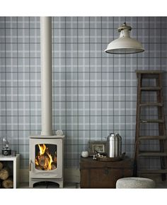 Light blue plaid wallpaper and grey accessories creates a cosy country living room.