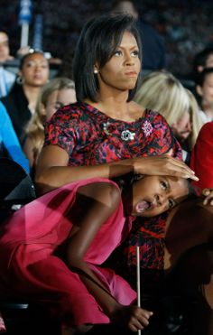 Sasha Obama yawns during her father Barack Obama's speech as Michelle Obama holds her head on day four of the Democratic National Convention (DNC) at Invesco Field at Mile High August 28, 2008 in Denver, Colorado. U.S. Sen.Photo Credit: Joe Raedle, Getty Images via StyleList