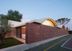 Curving vaults give Mesura's red brick extension to IV House in Spain's Alicante province a scalloped roofline.
